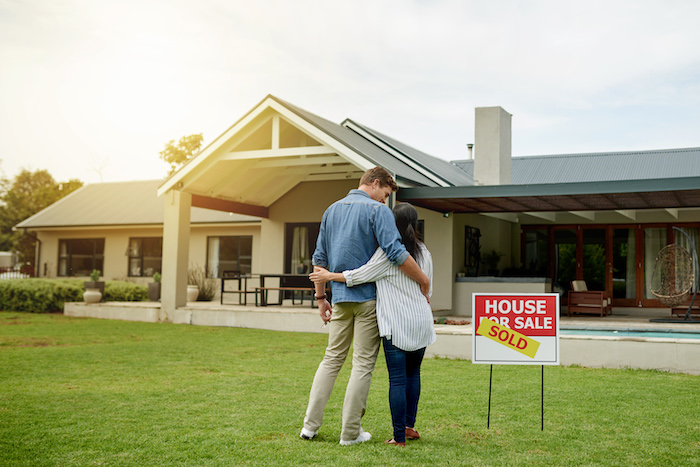 Couple Standing in Front of Sold House for Sale