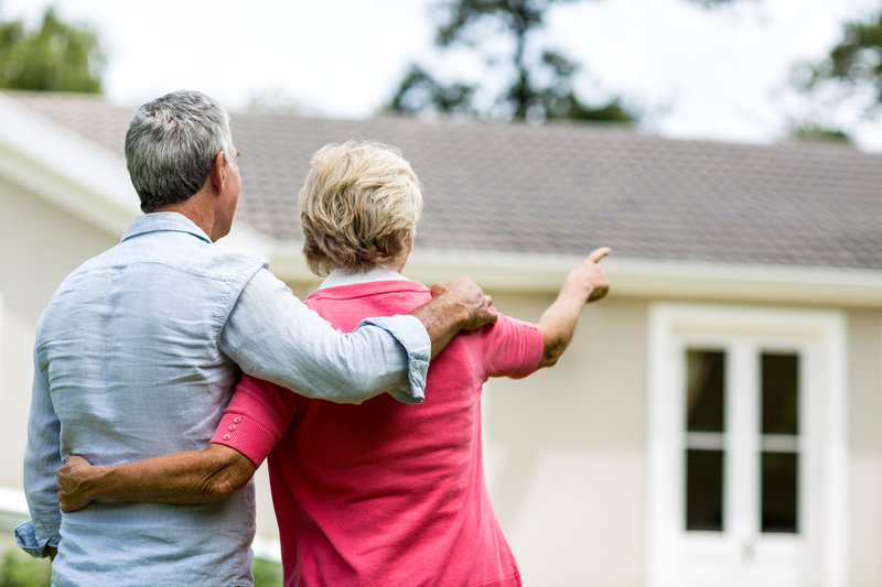 Older Couple Pointing at Homes
