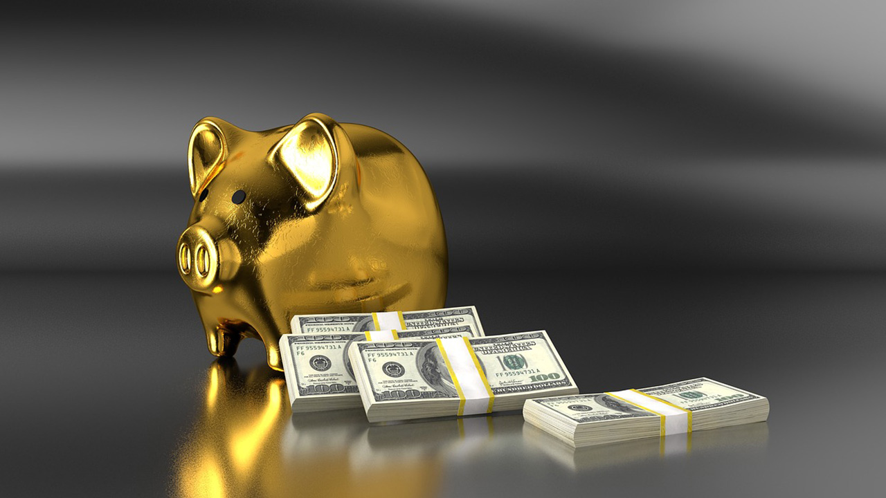 golden piggy bank with stacks of cash