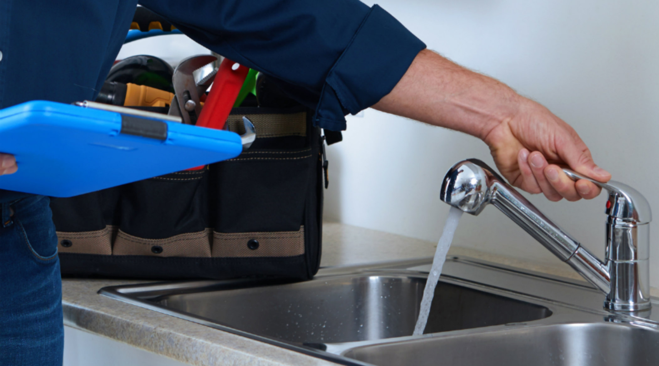 Inspector with blue clipboard and faucet1800x1000