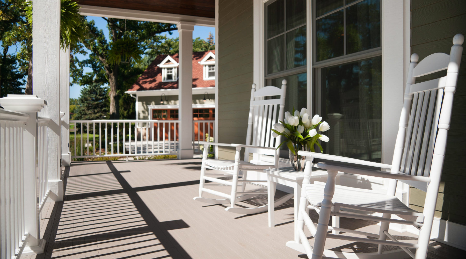 Front porch white rocking chairs and flowers