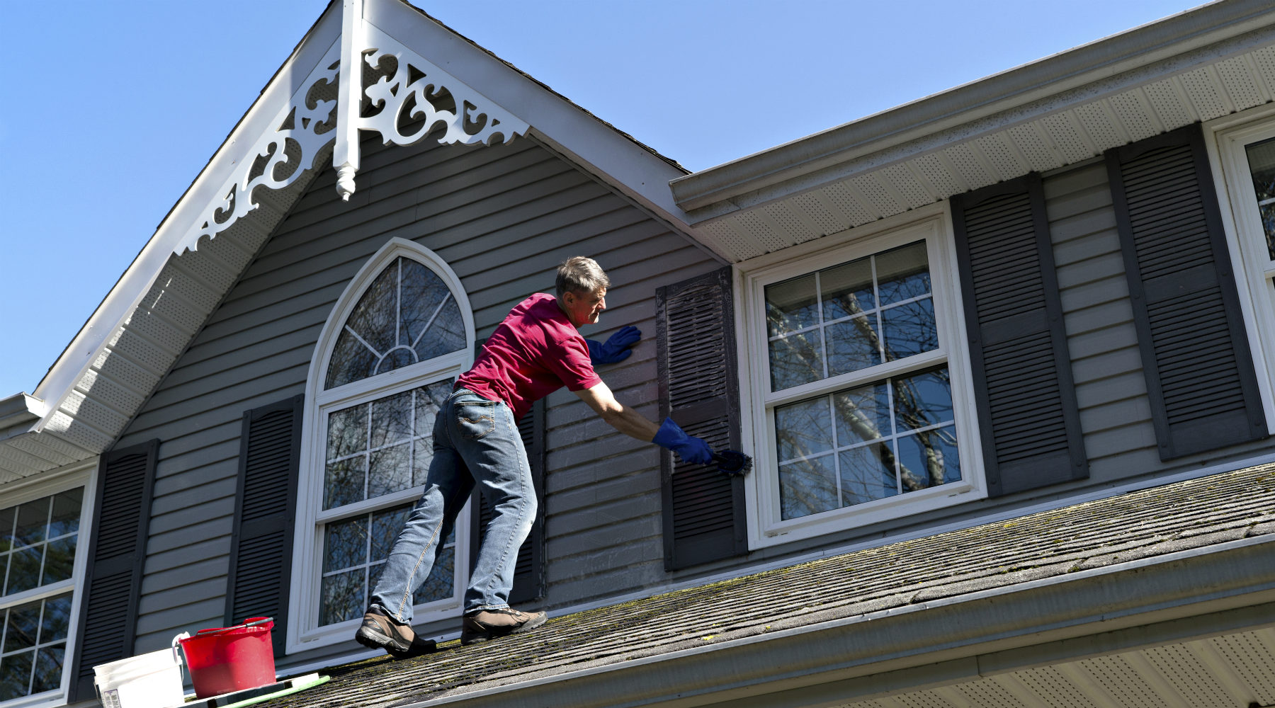Handyman on roof cleaning shutters
