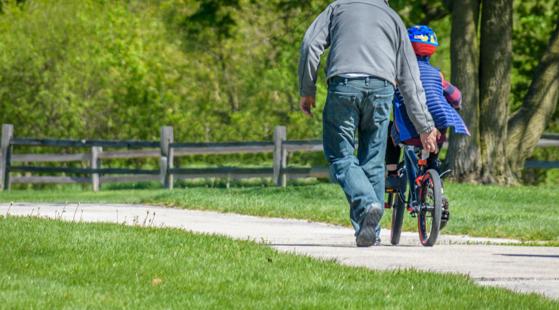 Man teaching little boy how to ride a bike