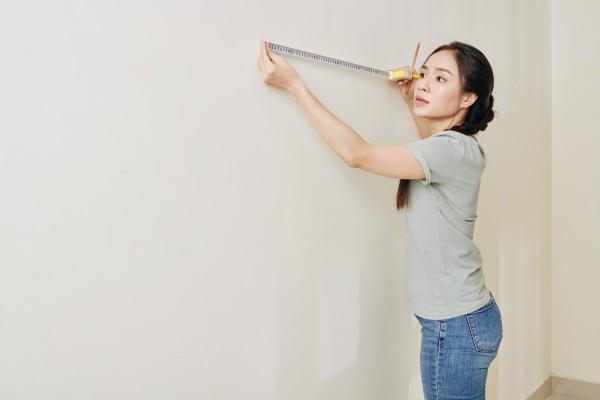 Woman Measuring a wall