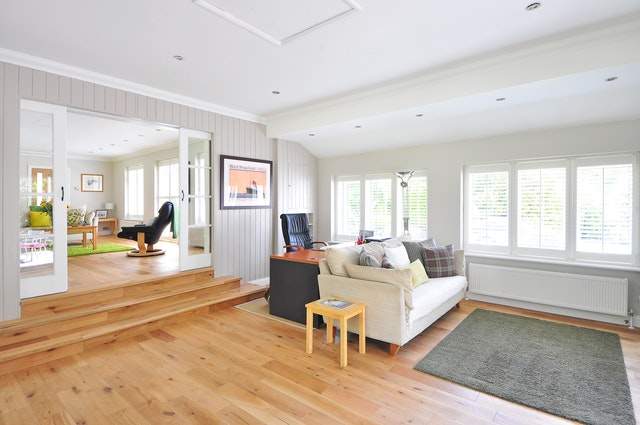 large living room with wood floors and steps to kitchen