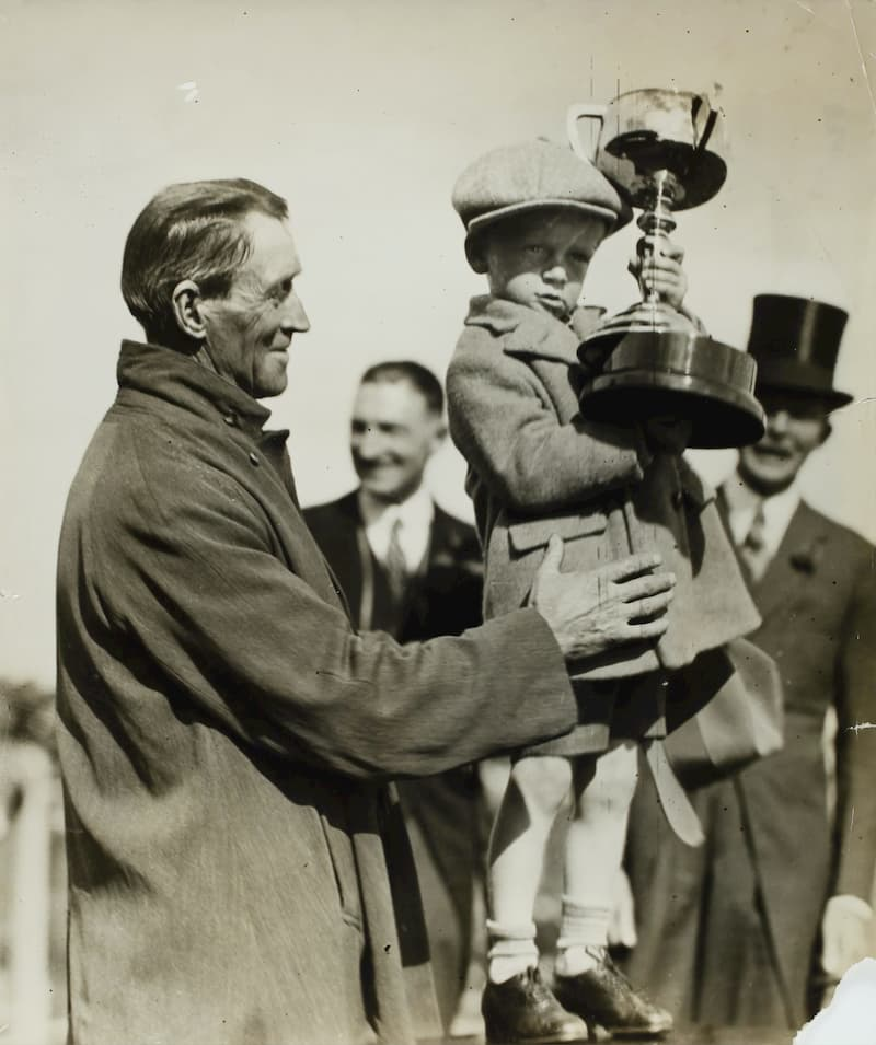 A little boy holding a trophy, and being held by a smiling older man, in 1930