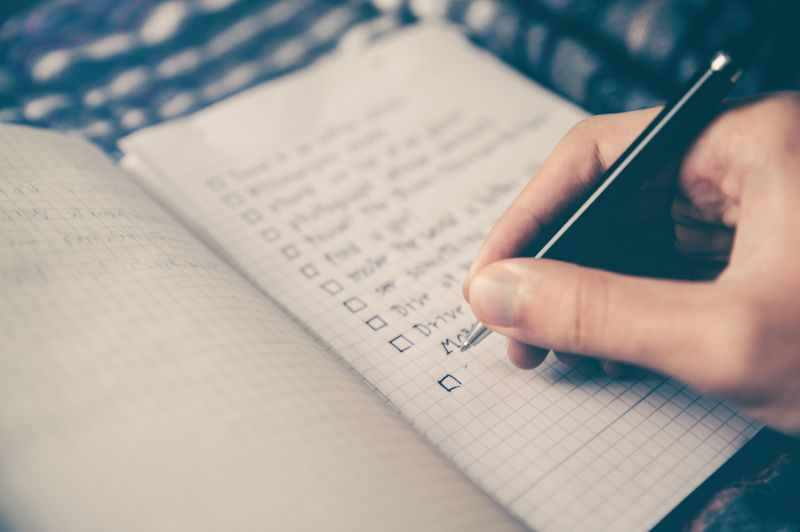 A handwritten checklist in a notebook