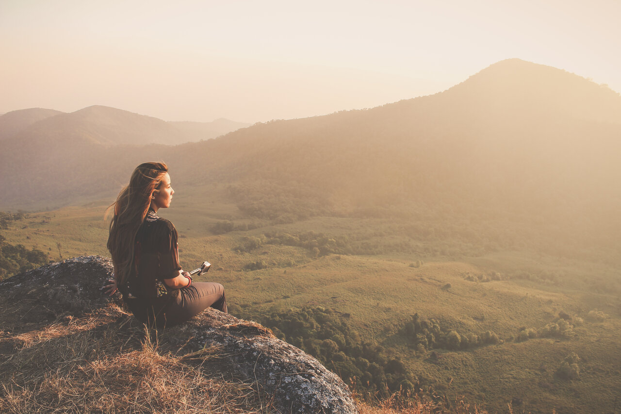 person sitting on rock looking at valley