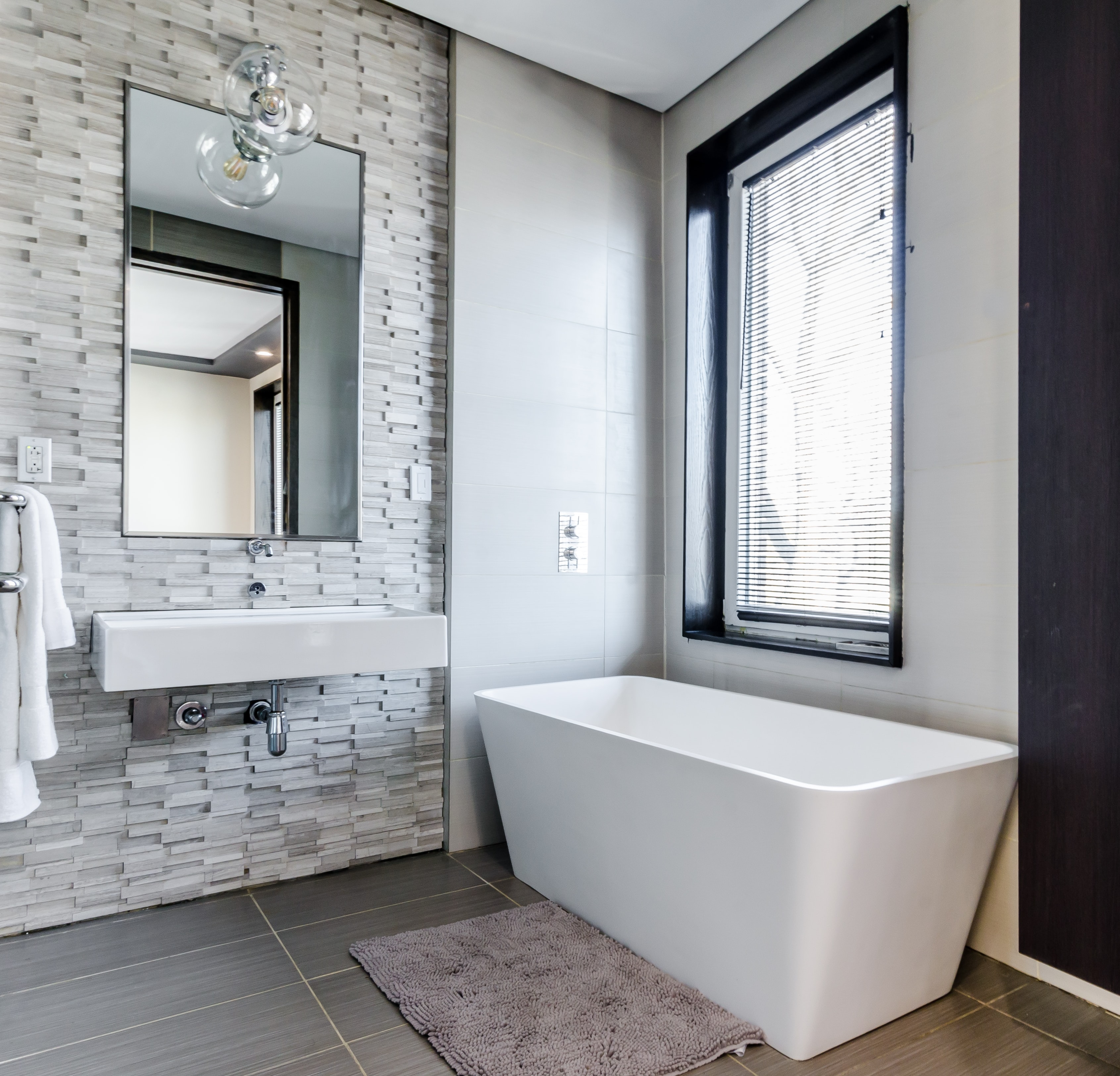 Bathroom with small bath and wall-mounted sink