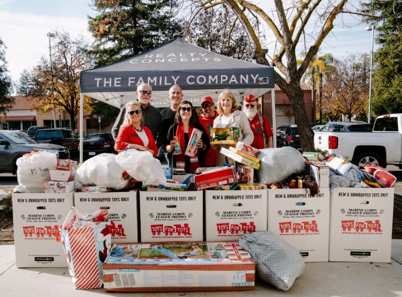 realty concepts agents and the toys for tots marine league standing behind the donated toys for our toy drive