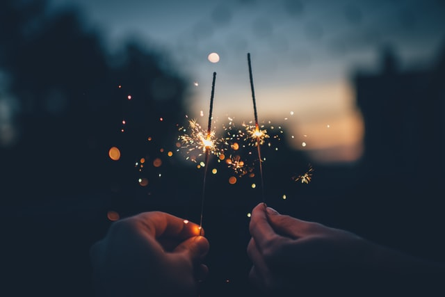 two hands holding sparklers at night