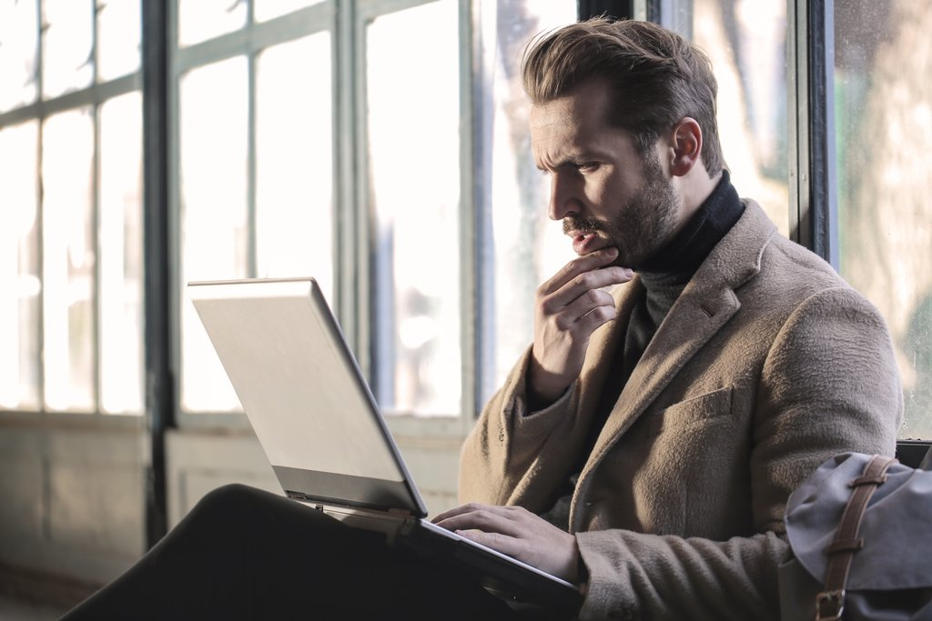 man looking at computer with hand on chin