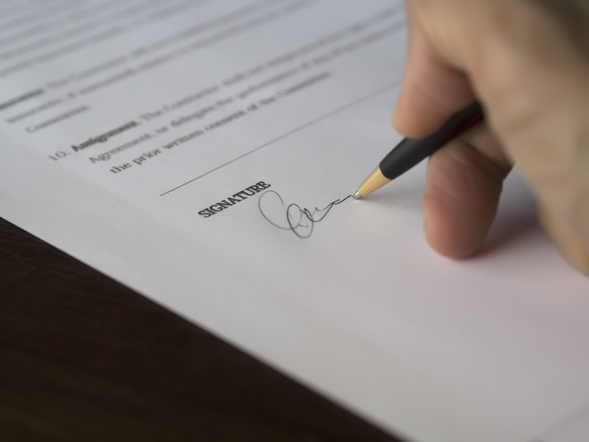 hand holding pen signing contract