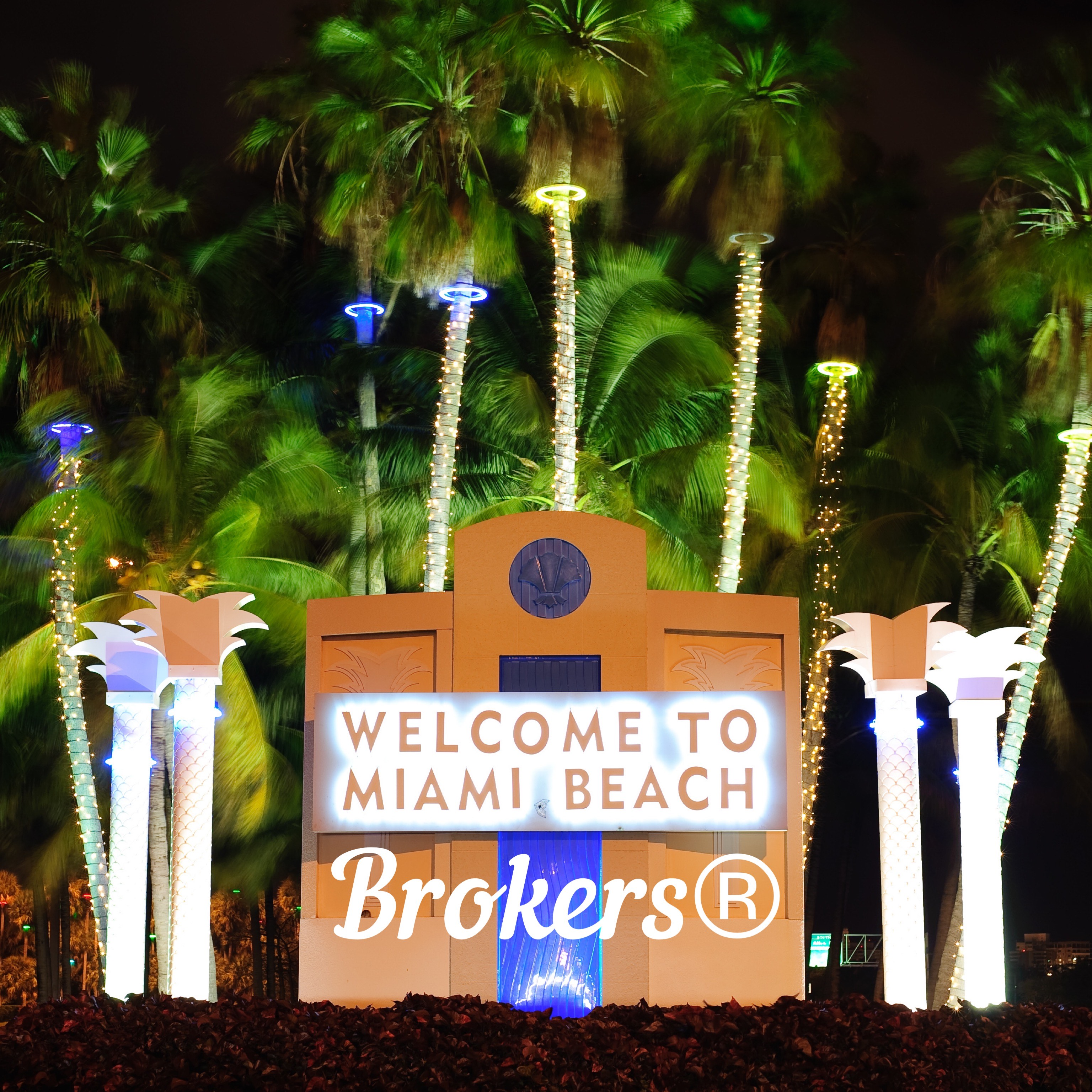 A night time picture of the WELCOME TO MIAMI BEACH sign modified, obviously, to read Welcome to Miami Beach Brokers®.  Miami Beach Brokers® is a registered trademark of Miami Beach Brokers LLC