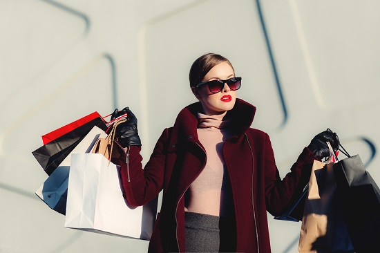 Woman who is wearing over-sized sunglasses is holding shopping bags in both hands.