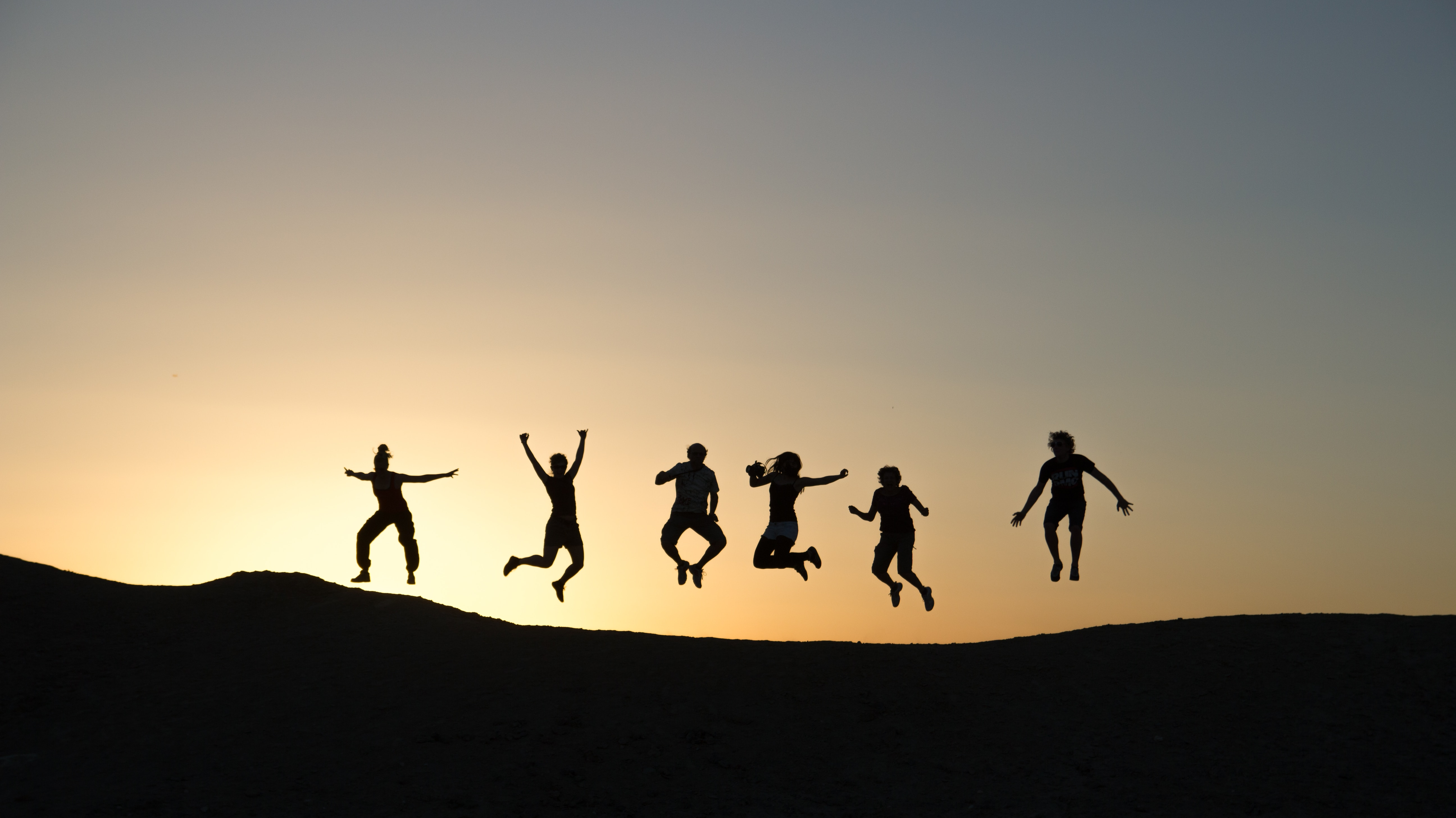 The silhouette of six people jumping against a sunset and a hill