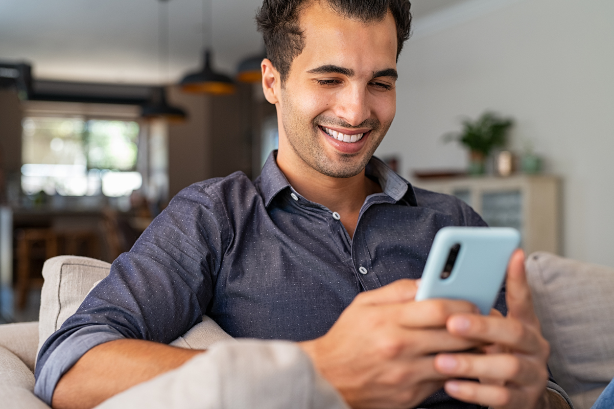 man smiling looking at phone