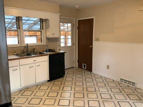 A kitchen with a tile floorDescription automatically generated